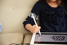 a girl drawing on an iPad