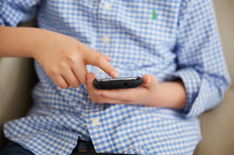 a boy with his finger on a cellphone screen