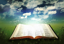twinkling light from a glowing Bible lying in grass under a blue sky