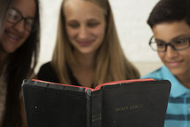 kids reading a Bible together