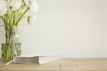 white flowers in a vase and Bible on a table