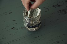 putting cash in a tithe savings jar