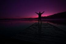 A man stands on a dock with his hands raised to the heavens.