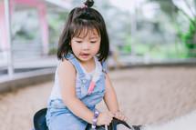 toddler girl riding a pony