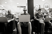 men on their laptops at a bookstore