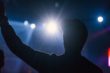 silhouette of a man with hands raised at a concert