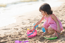 little girl playing in the sand on a beach