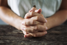 close up of woman with folded praying hands