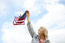 a young woman holding an American flag bandana