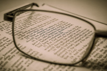 reading glasses on pages of a Bible