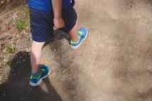 Boy walking on a park trail.