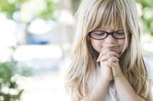 little blonde haired girl in prayer