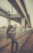 man standing on railroad tracks with a backpack