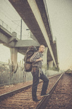 man backpacking standing on train tracks