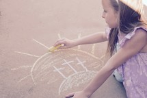 A little girl drawing three Easter crosses with sidewalk chalk