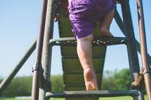 a toddler climbing up a slide
