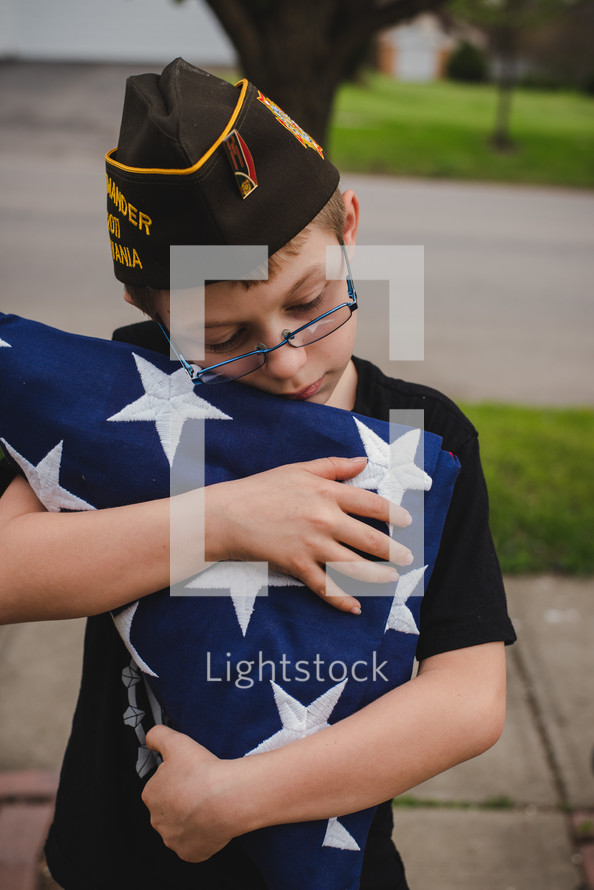 child carrying a folded flag and wearing a military cap