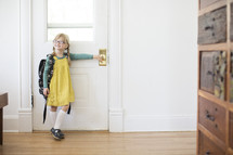 girl child standing at a door with a book bag - first day of school