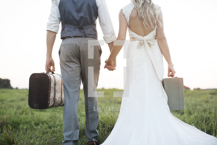 bride and groom carrying suitcases