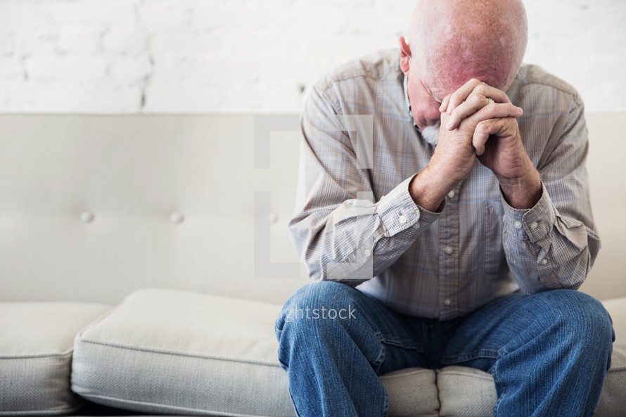 a man sitting on a couch with head bowed in prayer