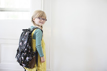 girl child with a book bag opening a door