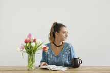 a woman sitting at a desk with a mug of coffee and a vase of tulips reading a book