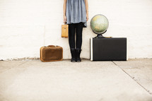 Girl holding a suitcase and standing next to a globe