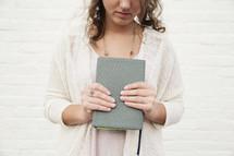 torso of a woman holding a Bible