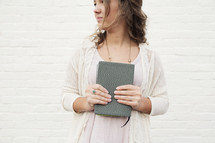 a young woman holding a Bible to her chest