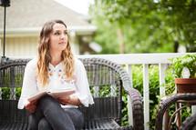 a woman sitting on a porch reading a Bible