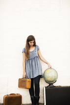woman holding luggage standing next to a globe