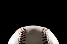 a baseball against a black background