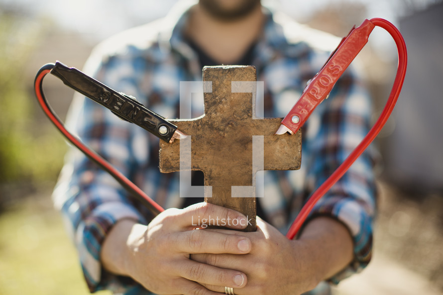 Man holding cross with jumper cables attached.