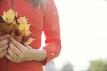 a woman holding a handful of fall leaves