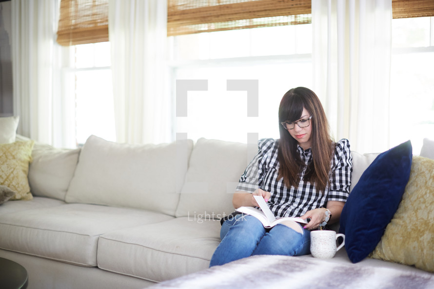 a woman sitting on a couch a Bible at home