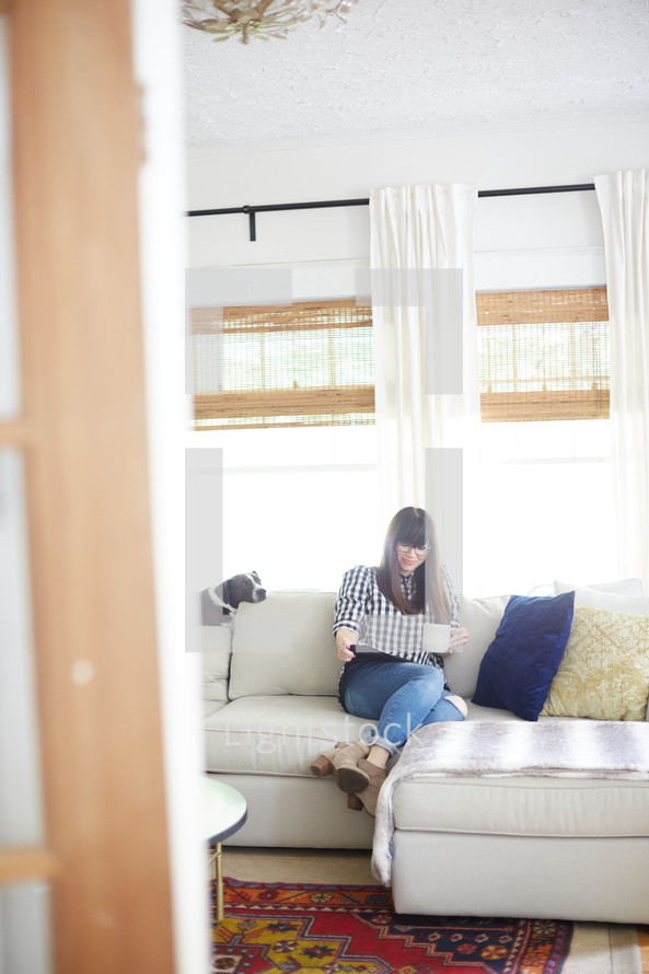 a woman sitting on a couch drinking coffee and looking at a tablet screen