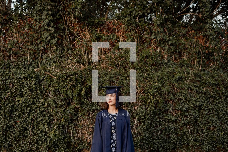 female graduate standing in front of vines