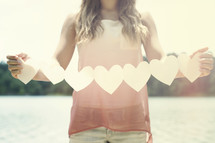 woman holding a chain of paper hearts