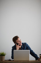 a man sitting behind a computer and talking on a cellphone