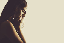 Pretty teenage girl with head bowed in prayer.