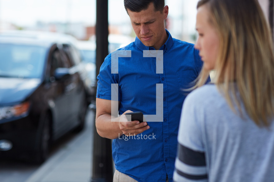 a man texting and a frustrated woman