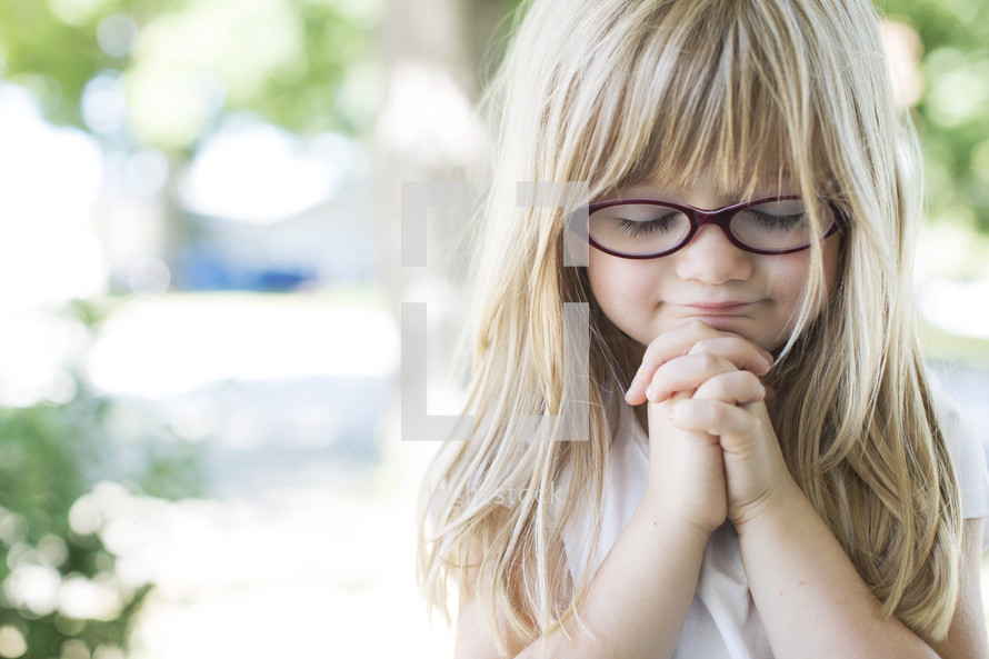 little blonde haired girl in prayer