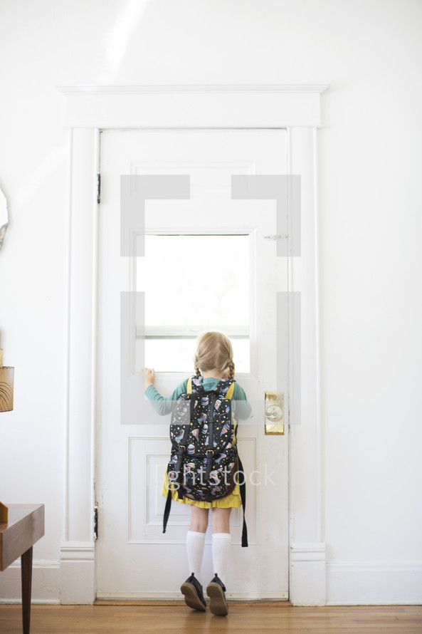 girl child with a book bag opening a door - first day of school