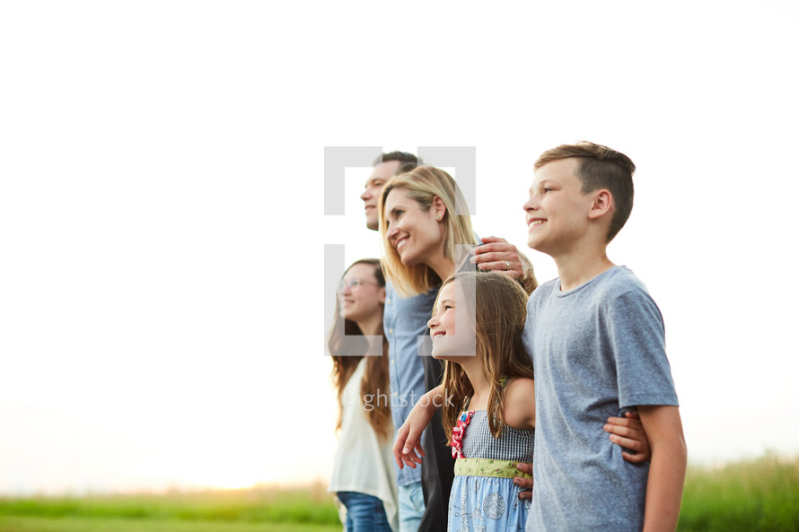 a family portrait standing outdoors at sunset