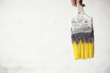 A used paint brush with yellow paint on the bristles.