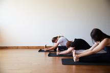 women stretching on yoga mats