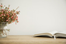 flowers in a vase and open Bible on a table