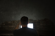 man looking at a computer screen in darkness.