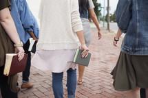 women walking carrying Bibles in the city.