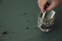 putting money into a tithe savings jar